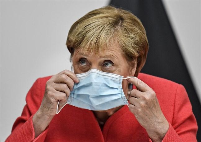 Angela Merkel tar på sig ett munskydd.