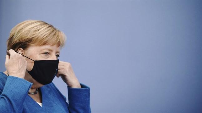 Tysklands förbundskansler Angela Merkel tar av sig sitt munskydd inför sin årliga sommarpresskonferens.