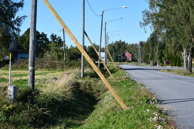 Belysningsstolpar vid Västra Härkmerivägen stöttas genom plankor placerade mot vägen, vilket är emot föreskrifterna.