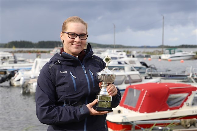 Minna Löfdahl, kassör i Oravais fiskargille, visar upp vandringspokalen för den fiskare som lyckas fånga den största gäddan.