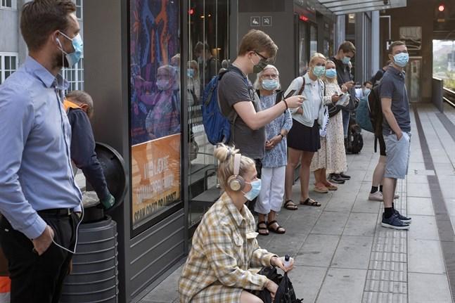 Passagerare med munskydd väntar på tåget i Århus i Danmark. Arkivbild.