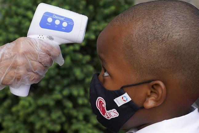 En pojke får sin temperatur mätt innan han släpps in i skolan i New York, USA.