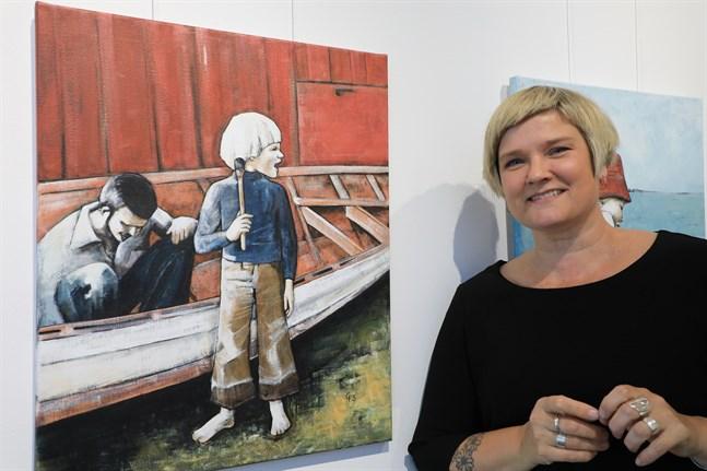 Camilla Forsén-Ström under två tidsepoker: som liten lintott i färd med att måla båten med pappa och som den konstnär som målat tavlan.