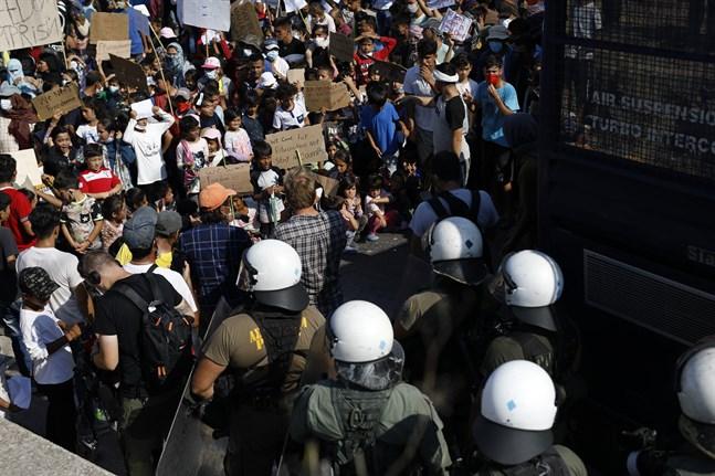 Poliser blockerar en väg nära Mytilene på Lesbos, där migranter protesterar.
