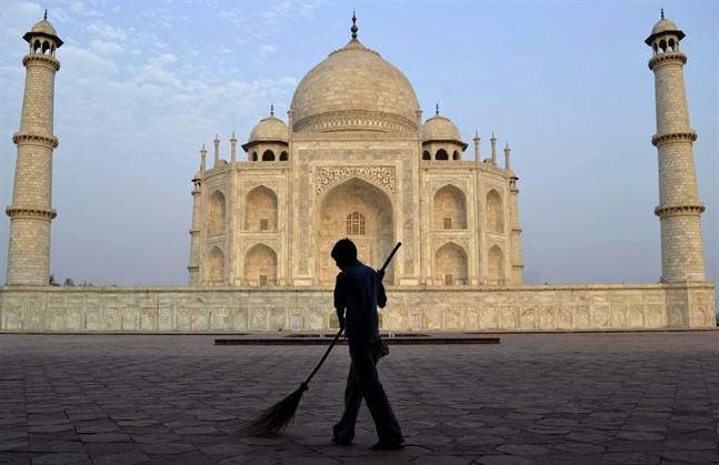 En arbetare sopar framför Taj Mahal. På måndagen öppnar Indiens populäraste turistattraktion för besökare, efter att ha hållit stängt på grund av covid-19. Arkivbild.