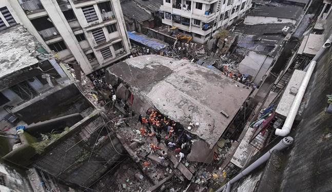 Räddningsarbetare vid den kollapsade byggnaden i Indien.