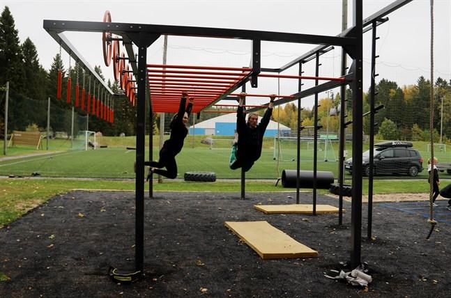 Amanda Örn och Lasse Lorentz demonstrerar monkey bar och flying monkey på den nya träningsriggen vid Norrvalla.