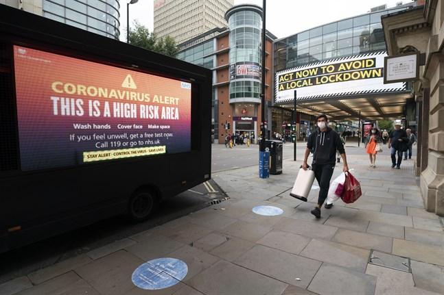 Varningsskyltar bland handlande människor i centrala Manchester i norra England i tisdags.