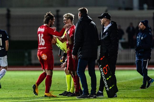 Topi Järvinen ersätts av Axel Vidjeskog med en kvart kvar att mötet mellan Jaro och AC Oulu. Niklas Käcko och Christian Gunnar övervakar bytet, medan AC Oulu-tränaren Jyrki Ahola syna i bakgrunden.