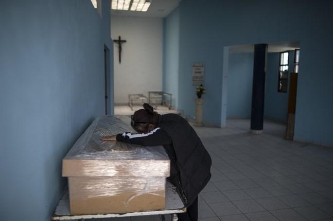 En änka sörjer sin make, som avlidit efter att ha insjuknat i covid-19, i Perus huvudstad Lima.