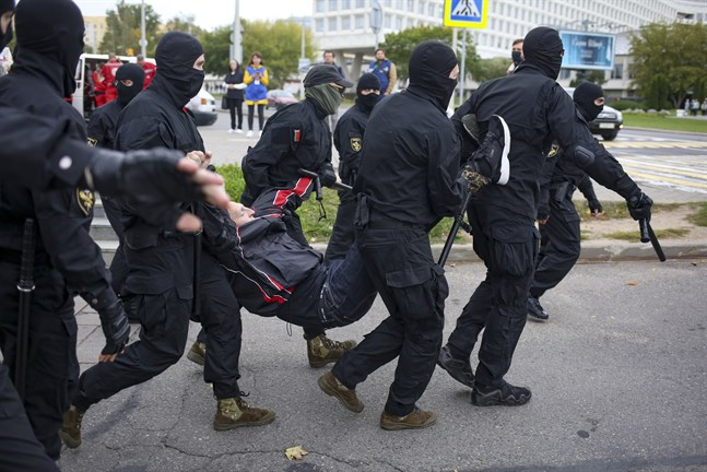Polisen i Belarus griper en demonstrant i Minsk under söndagens massprotest.