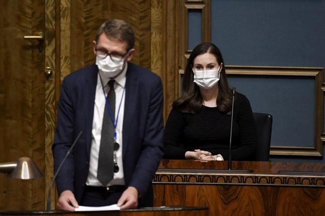 Finansminister Matti Vanhanen (C, i förgrunden) och statsminister Sanna Marin (SDP) försvarade regeringens politik mot oppositionens kritik på onsdagen.
