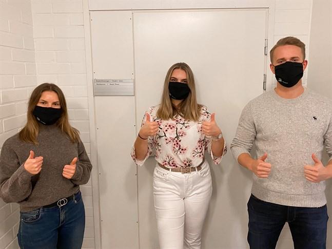 Studenterna Frida Stenbacka, Lisa Niemistö och Felix Anderson med sina Hanken-masker.