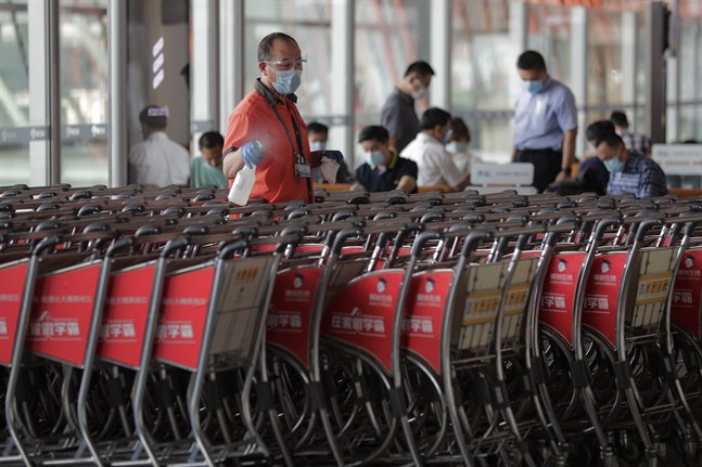 En flygplatsarbetare desinficerar bagagevagnar på Pekings internationella flygplats. Bilden är från den 8 september.