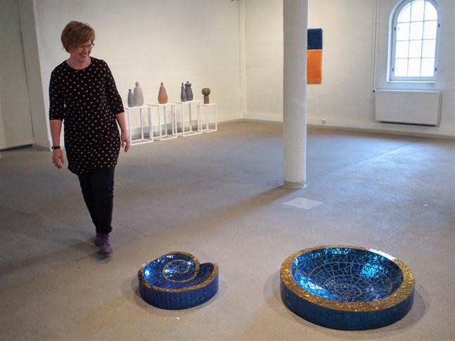 """Glaskonstnären Minna Tuohisto-Kokko med två av sina verk från utställningen """"Sininen konsti""""."""