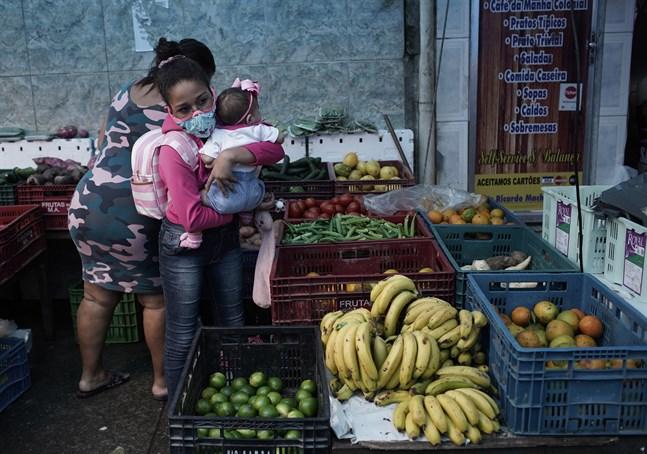 En kvinna med en bebis köper frukt i Rio de Janeiro.