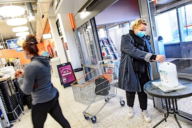 Sara Lindvall och Kajsa Mattbäck spritar omsorgsfullt händerna på väg in i affären.