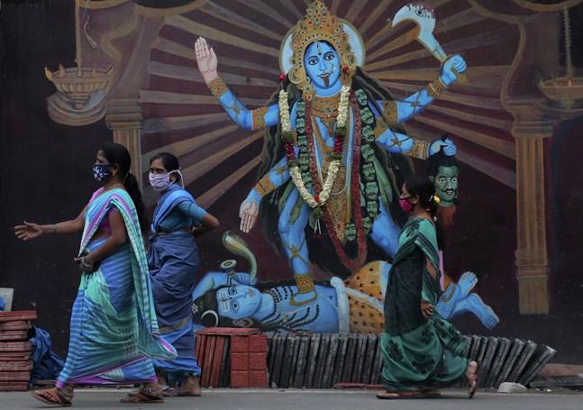 Indiska kvinnor passerar ett altare till gudinnan Durga i Hyderabad. Antalet coronasmittade i Indien har passerat sju miljoner, när hinduernas festivalsäsong just ska börja.