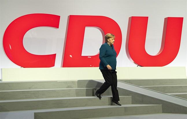 Tre män kandiderar för att ta över kristdemokratiska CDU och i förlängningen sannolikt bli Tysklands förbundskansler efter Angela Merkel. Här går Merkel på scenen vid partikongressen 2019.