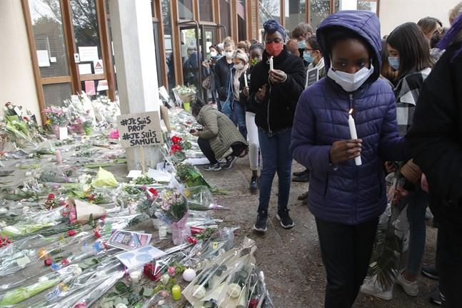 Blommor och tända ljus utanför skolan i Parisförorten Conflans-Sainte-Honorine, där en lärare mördades i fredags.