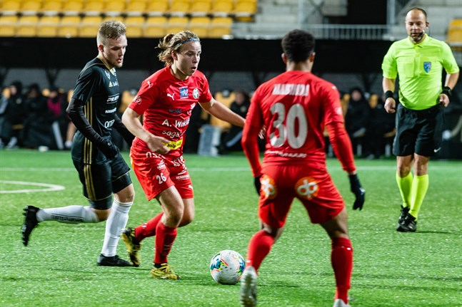 Marcel Wargh driver med bollen för Jaro mot SJK Akatemia i oktober 2020. I förgrunden Jean Mabinda.