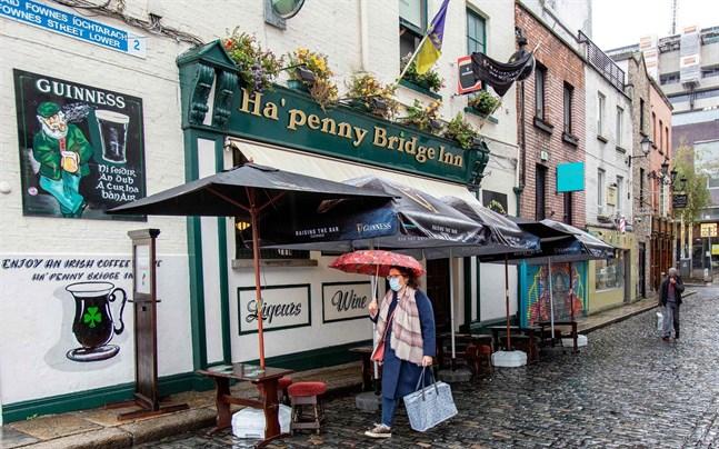 En kvinna passerar en nedstängd pub i Irlands huvudstad Dublin på måndagen.