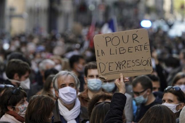 """En man håller upp ett plakat med texten """"För yttrandefrihet"""" vid en demonstration till stöd för den mördade läraren Samuel Paty, i Lyon."""