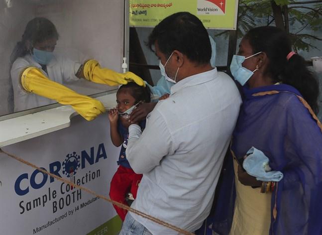 Vårdarbetare testar en familj för coronaviruset i indiska Hyderabad i oktober.