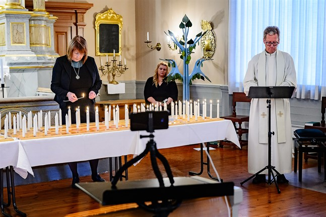 Diakonissan Helena Ekman tänder ljus medan Jockum Krokfors läser upp namnen. Cecilia Åminne i bakgrunden. Parentationen i Jakobstads kyrka är endast virtuell i år.