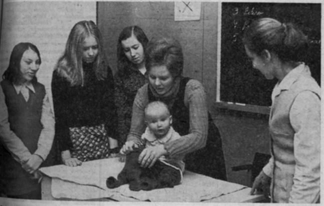 Här jobbar Kirsti Laasanen som är hemma i Vasa med att få kläderna på igen efter blöjbyte medan lärarinnan, sjuksköterskan Litti Wahlbeck från Vasa (t.h.) och Rosita Utter (Tjöck), Harriet Lindelöf och Ingemo Granskog (Skaftung) noga följer med händelseförloppet.