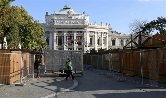 Arbetare bygger ett staket runt julmarknaden framför Burgtheater i Wien, vars öppning har skjutits upp på obestämd framtid.