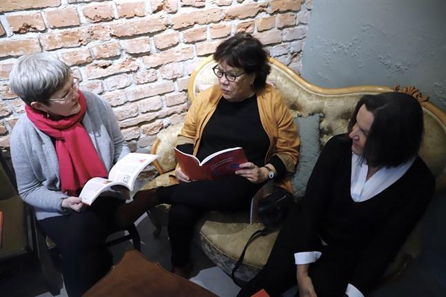 Berit Öhman, Camilla Berggren och Gun-Britt Lund sitter med den färdiga historiken över Vasa svenska kvinnoklubbs drygt hundraåriga historia.