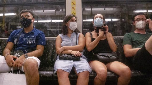 Passagerare med munskydd i Berlins tunnelbana.