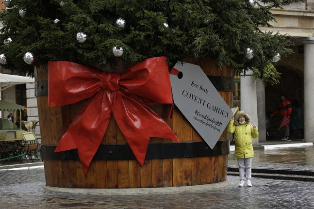 En kvinna med munskydd fotograferas tillsammans med en julgran vid Covent Garden i London i Storbritannien.