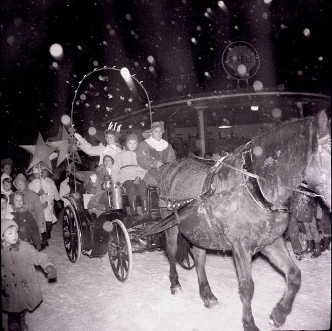 Lucian 1960 Vivan Hassel åker i snöväder i vagnen längs Styrmansgatan förbi Shellstationen, som idag är en pub med uteterass.
