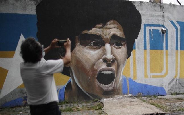 En man tar en bild vid en mur i Buenos Aires med ett gigantiskt Maradona-porträtt.