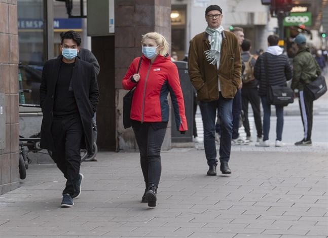 Människor iförda munskydd på Kungsholmen i Stockholm. Arkivbild.