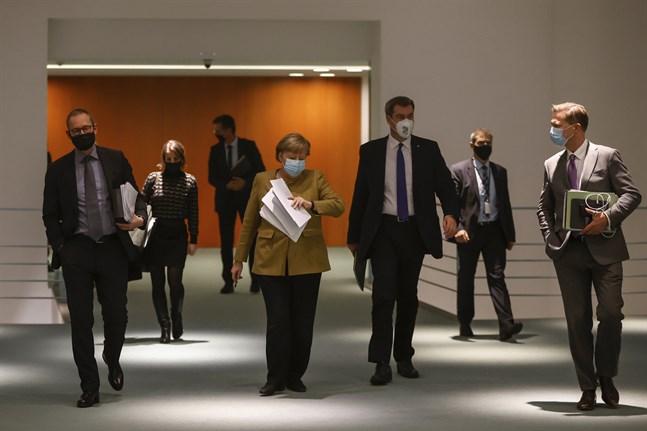 Angela Merkel (i mitten) på väg till presskonferensen där de nya coronaåtgärderna presenterades.