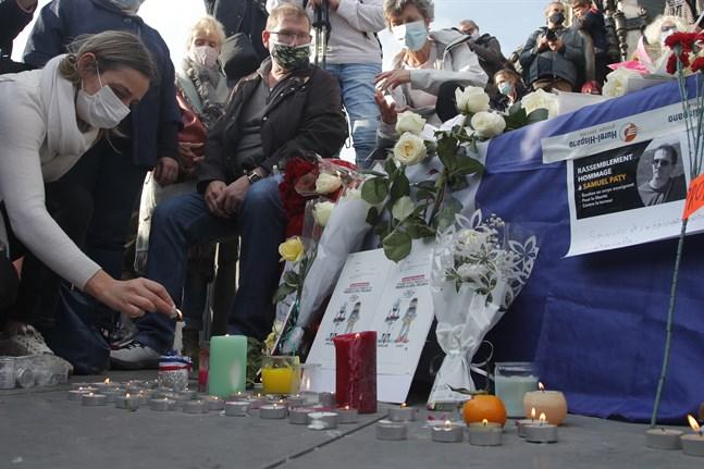 En kvinna tänder ett ljus under en demonstration i Paris efter mordet på Samuel Paty. Arkivbild.