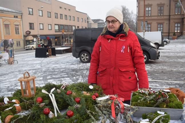 Gudrun Nyman erbjuder julkransar och hantverk vid sitt försäljningsbord på julmarknaden.
