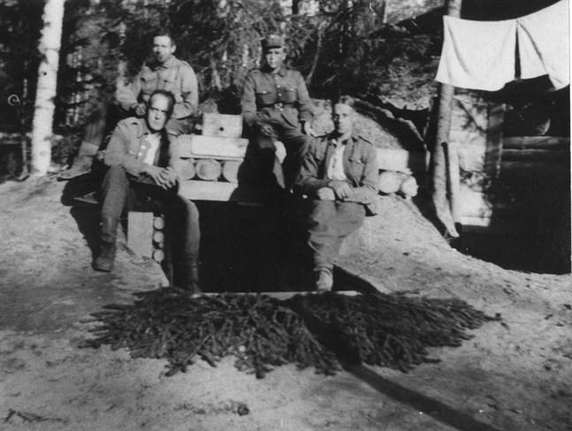 """Kanonkompaniets korsu """"Arken"""" på Lobacken i Schemenski på Sviravsnittet. I dörröppningen till höger sergeant Gösta Sundqvist och bredvid honom korpral August Villfors. På taket sitter soldat Ernfrid Ek (till höger) och korpral Holger Ljung."""