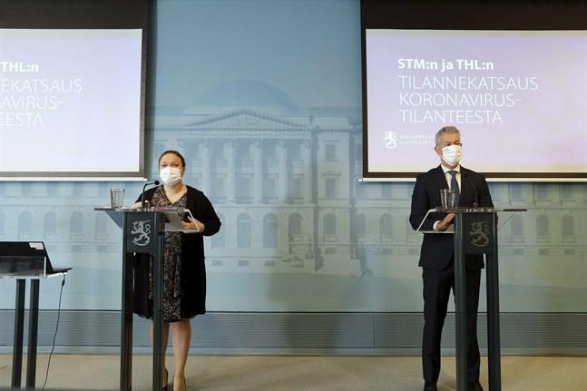 Familje- och omsorgsminister Krista Kiuru (SDP) och THL:s överläkare Taneli Puumalainen vid torsdagens presskonferens om coronaläget.