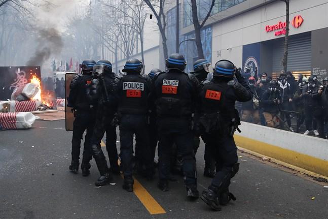 Kravallpolis närmar sig en brinnande barrikand under lördagens våldsamma protester i Paris.