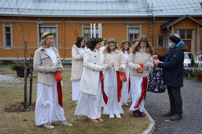 Torof Back delar ut godispåsar till lucia och tärnor i Kristinestad. De lussade utomhus, medan publiken stod på långt avstånd eller inomhus.