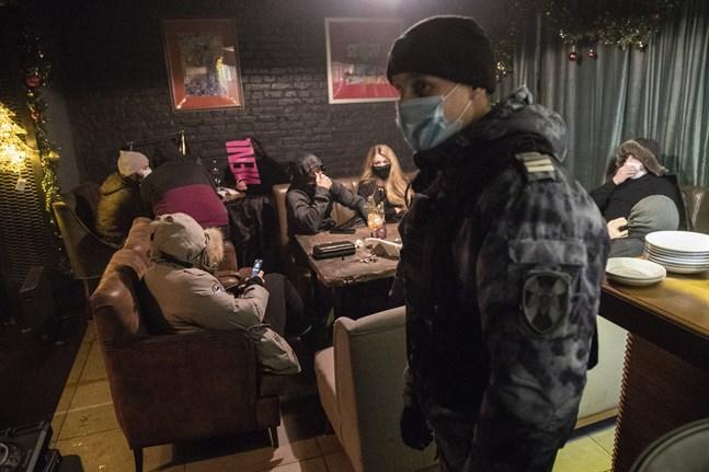 En polis inspekterar en bar i Moskva som brutit mot lokala restriktioner under julhelgen. Bilden är från den 26 december.