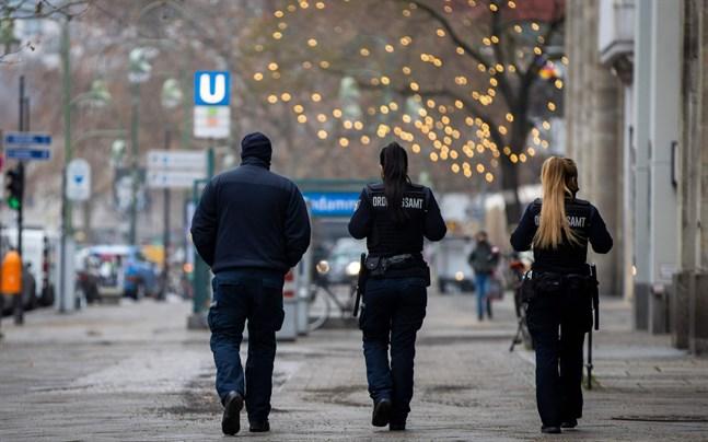 Ordningsvakter patrullerar längs Kurfuerstendamm i Berlin för att kontrollera att alla restriktioner följs.