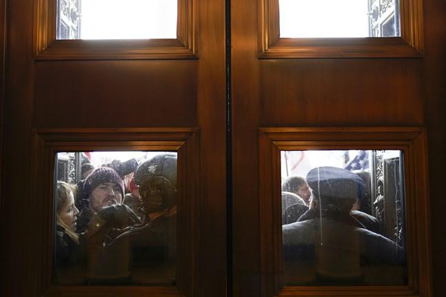 Polisen försöker hålla tillbaka protesterande Trumpanhängare utanför kongressen i WashingtonDC.