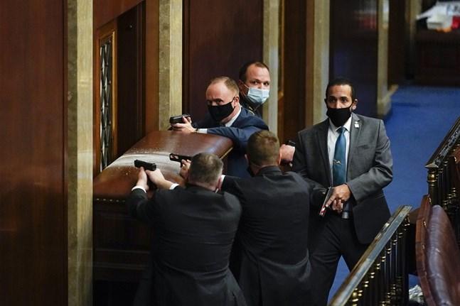 Poliser i Kapitolium med dragna vapen, medan de försöker hålla demonstranter ute ur representanthusets kammare.