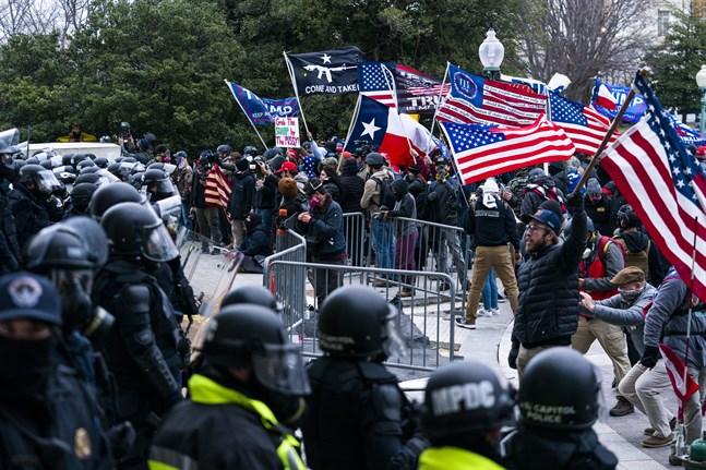 Anhängare till president Donald Trump möts av kravallklädd polis utanför Kapitolium den 6 januari, strax innan stormningen av kongressen.