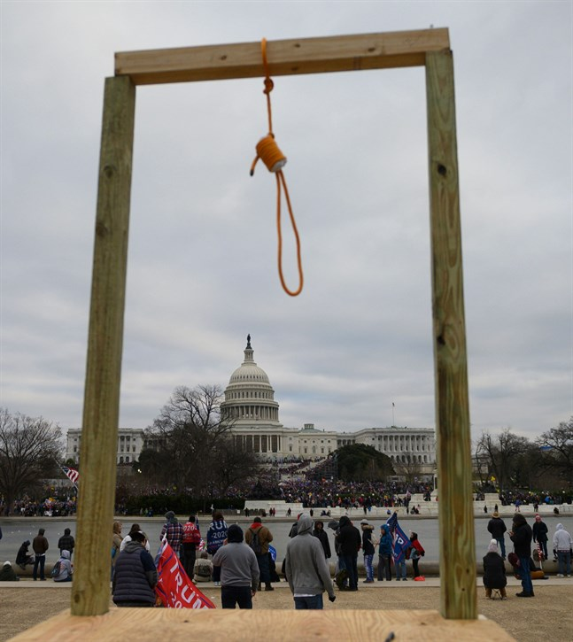 Så här såg det ut strax väster om Capitolium den 6 januari. En bild som andas Ku Klux Klan från förra seklet. Ställningen är byggd av Donald Trumps anhängare. Av dem som tror på Qanons läror.
